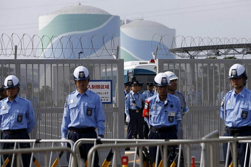 Police officers and security personnel stand guard at an entrance of Kyushu Electric Power's Sendai nuclear power station.