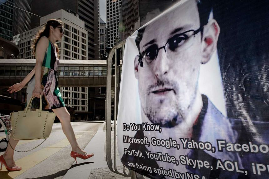 A 2013 photo shows a woman walking past a banner displayed in support of US intelligence whistleblower Edward Snowden in Hong Kong.