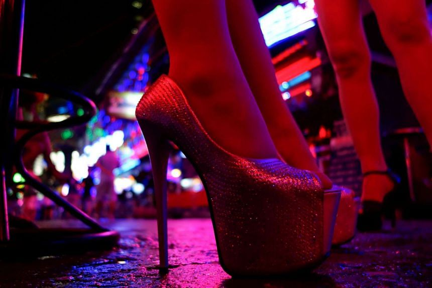 Women stand outside a bar in a red light district in Bangkok, Thailand, July 12, 2016.