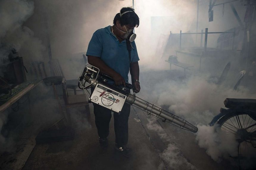 A city worker sprays chemicals with a fumigator to kill mosquitoes in an effort to control the spread of the Zika virus at a school in Bangkok on Sept 14.