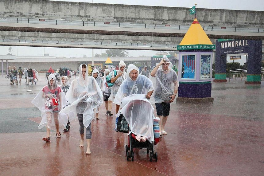 People leaving Disney's Magic Kingdom theme park, in heavy rain, after it closed in Orlando, Florida in preparation for the landfall of Hurricane Matthew, on Oct 6.