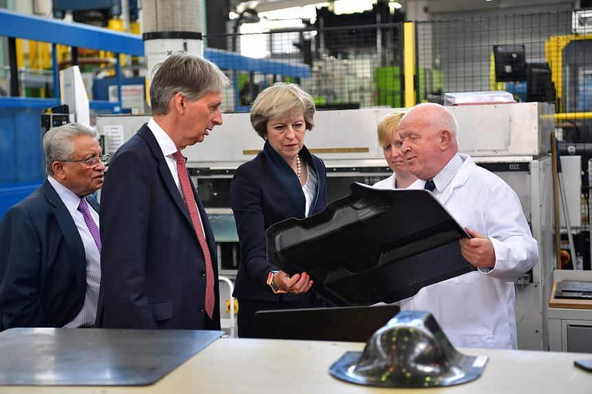 British Prime Minister Theresa May (center) meet technicians during a visit to the Warwick Manufacturing Group facility at the University of Warwick on Sept 1, 2016.