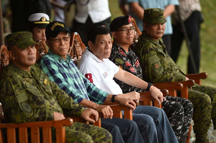 Philippine President Rodrigo Duterte (in white) with Defence Secretary Delfin Lorenzana (second from left), who announced on Friday (Oct 7) the country has suspended South China Sea patrols with the United States.