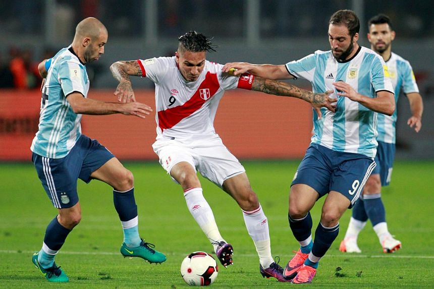 Peru's Paolo Guerrero (center) is challenged by Argentina's Javier Mascherano (left) and Gonzalo Higuain.