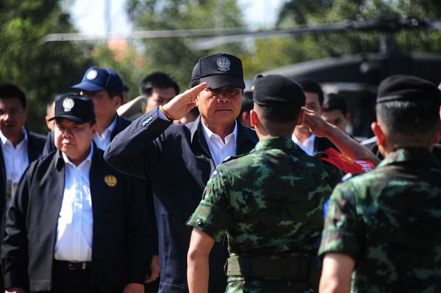 Thai Prime Minister Prayuth Chan-Ocha is greeted by military officers during a visit to Thailand's restive southern province of Narathiwat on July 25, 2016.