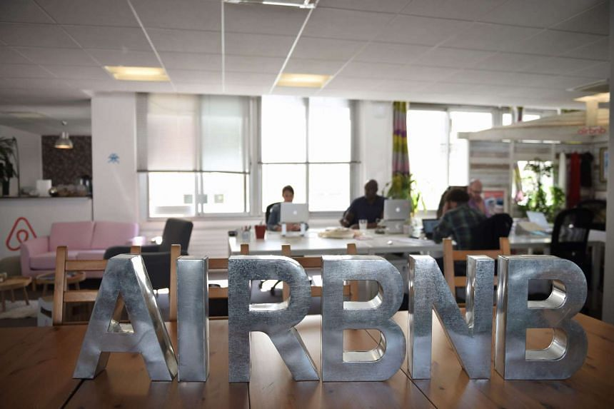 This file photo taken on April 21, 2015 in Paris shows employees of online lodging service Airbnb working in the Airbnb offices.