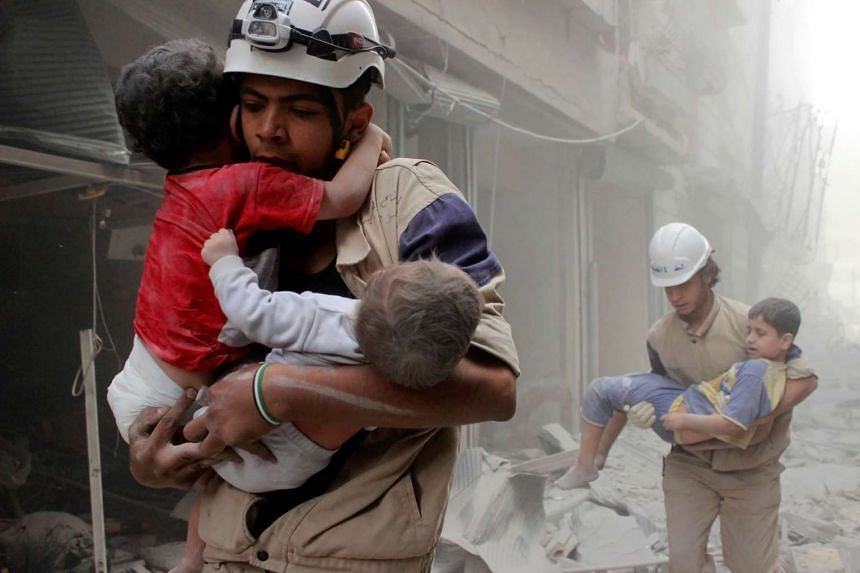 Members of the Civil Defence rescue children after what activists said was an air strike by forces loyal to Syria's President Bashar al-Assad in al-Shaar neighbourhood of Aleppo, Syria on June 2, 2014.