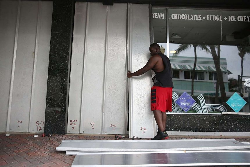 Kevin Hunter puts up hurricane shutters in front of a business as Hurricane Matthew approaches the area on Oct 6, 2016 in Delray Beach, Florida.