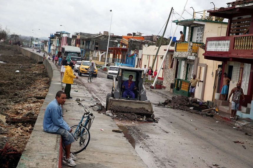 Cubans pick up the pieces following the damage and havoc caused by Hurricane Matthew in Baracoa, Cuba, on Oct 6, 2016. Matthew has crossed over parts of Haiti and Cuba and is expected to move up the east coast of the United States.