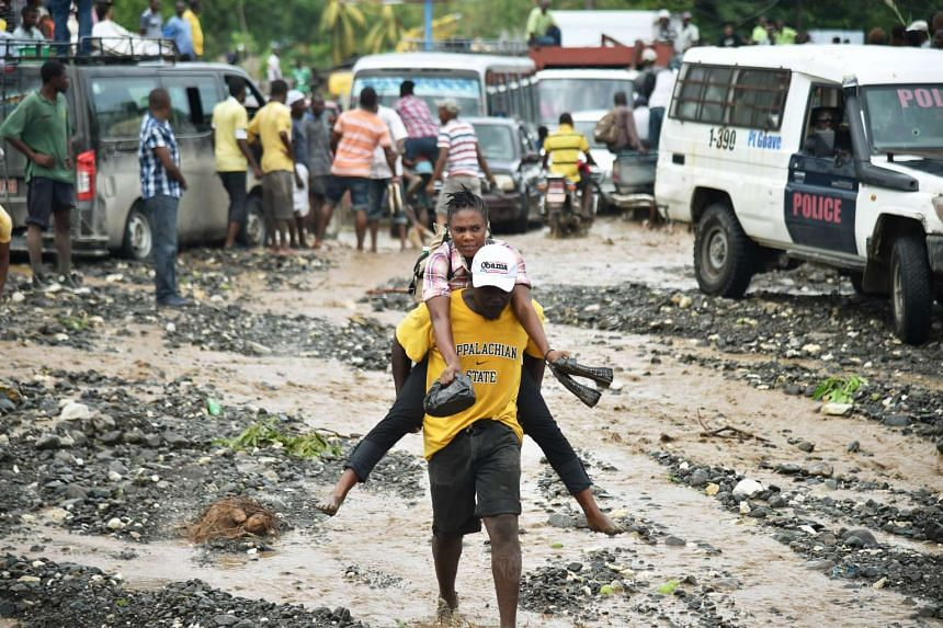Haitian people cross the river La Digue in Petit Goave where the bridge collapsed during the rains from Hurricane Matthew, southwest of Port-au-Prince, on Oct 6, 2016.