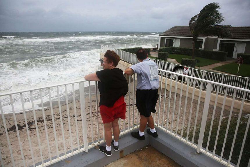 Karen Lanman and Don Lanman look out at the churning ocean as Hurricane Matthew approaches the area on Oct 6, 2016 in Jupiter, Florida.