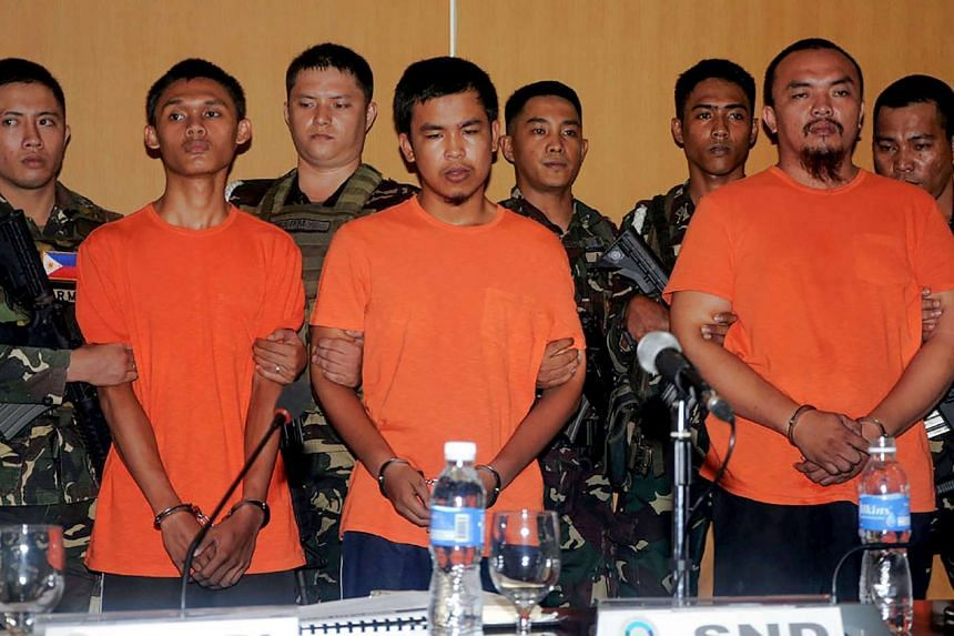 Three members of a Muslim extremist group (from left) TJ Tagadaya Mcabalang, Musali Mustapha and Wendel Apostol Facturan are presented during a press conference at the Department of National Defence (DND) headquarters at Camp Aguinaldo in Manila on O