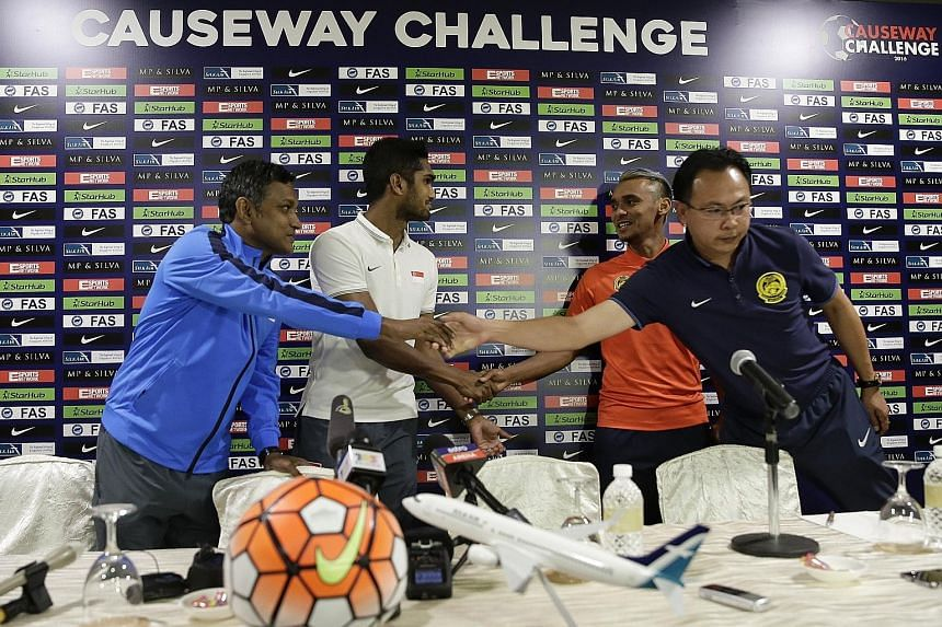 Lions coach V. Sundramoorthy (left) and captain Hariss Harun extend greetings to Malaysian counterparts Ong Kim Swee and Amri Yahyah.