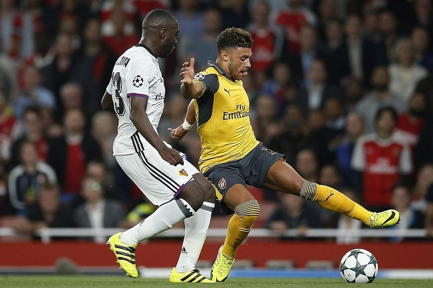 Arsenal midfielder Alex Oxlade-Chamberlain (right) going up against Basel defender Eder Balanta in the Champions League. He was a substitute in the 2-0 win and has yet to nail down a starting spot at Arsenal.