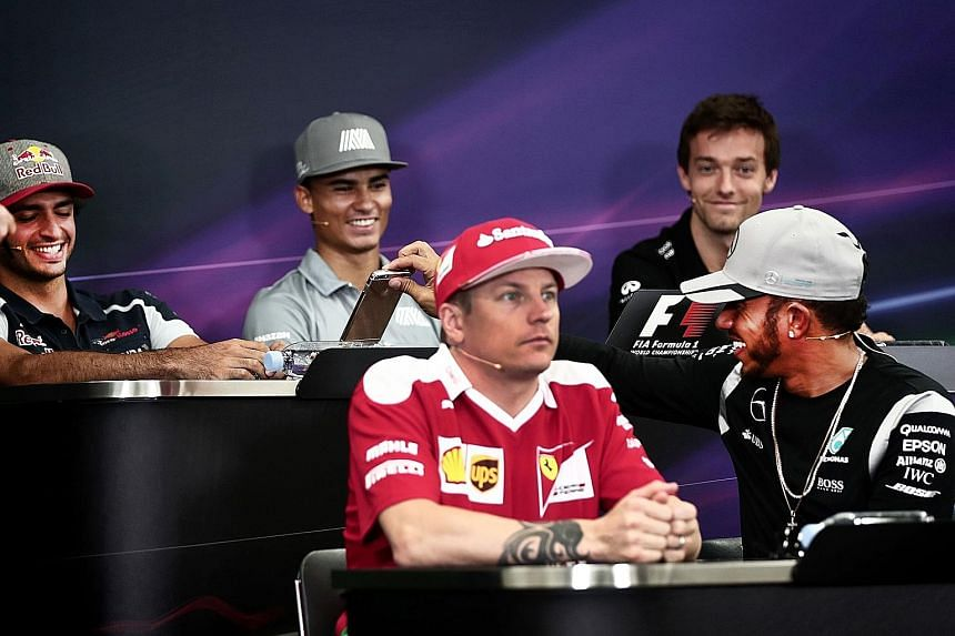 Left: Mercedes driver Lewis Hamilton (front, right) shows his phone to Toro Rosso's Carlos Sainz Jr at a press conference with Ferrari's Kimi Raikkonen (front, left), Manor's Pascal Wehrlein (centre) and Renault's Jolyon Palmer. Above: Lewis Hamilton