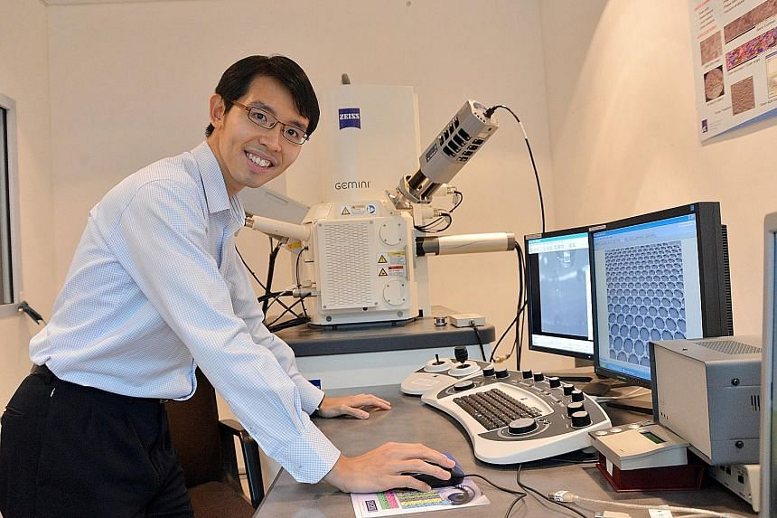 Dr Wong Liang Jie with a scanning electron microscope which the researchers use to check graphene for defects and to make sure it really is a single layer of atoms.