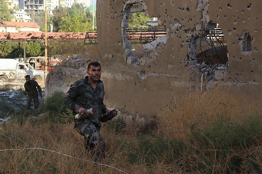 A Syrian pro- government soldier carrying homemade bombs in Aleppo's rebel-held Bustan al-Basha area yesterday.