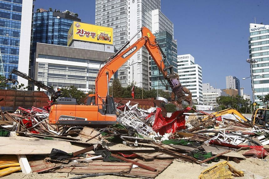Debris from structures erected on Haeundae beach, the venue for the Busan International Film Festival, being cleared away yesterday. Festival events had to be cancelled or moved indoors.