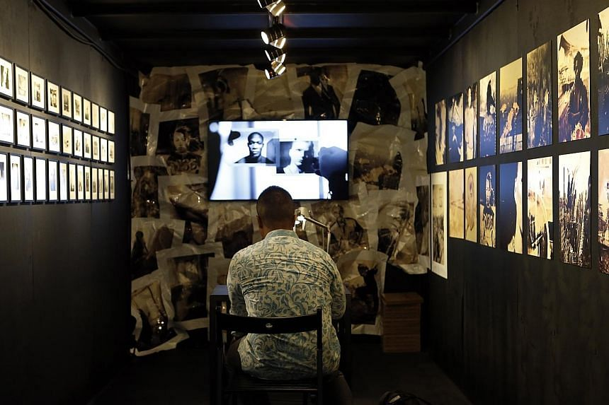 A visitor at the fifth Singapore International Photography Festival admiring Proof - a collection of contact proofs from photographic film - by award-winning Polish documentary film-maker and photographer Tomasz Gudzowaty. The work is part of the Arc