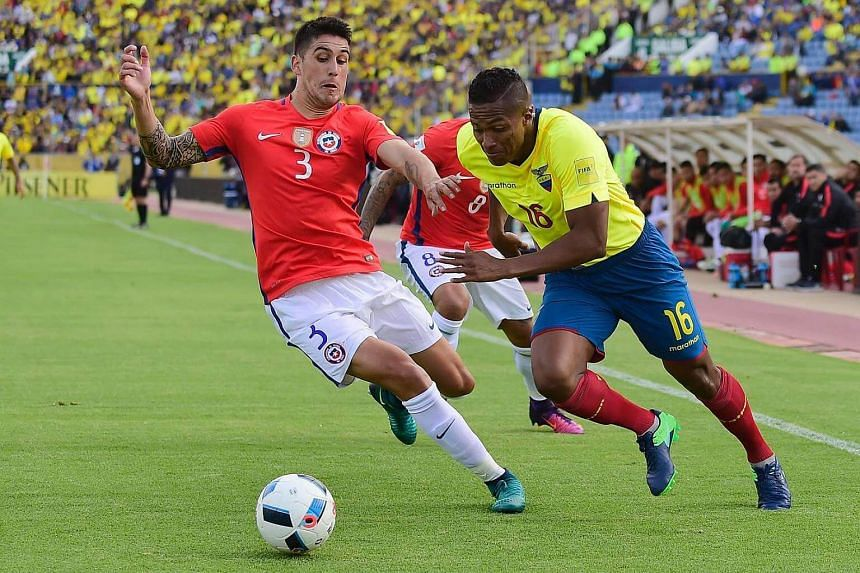 Chile's Enzo Roco (left) and Ecuador's Luis Antonio Valencia vie for the ball during their Russia 2018 World Cup football qualifier match in Quito, on Oct 6, 2016.