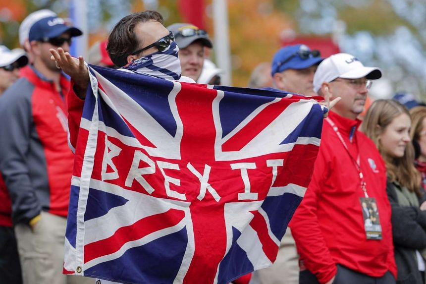 A golf fan holds a Brexit flag during practice for the 2016 Ryder Cup on Sept 29, 2016.