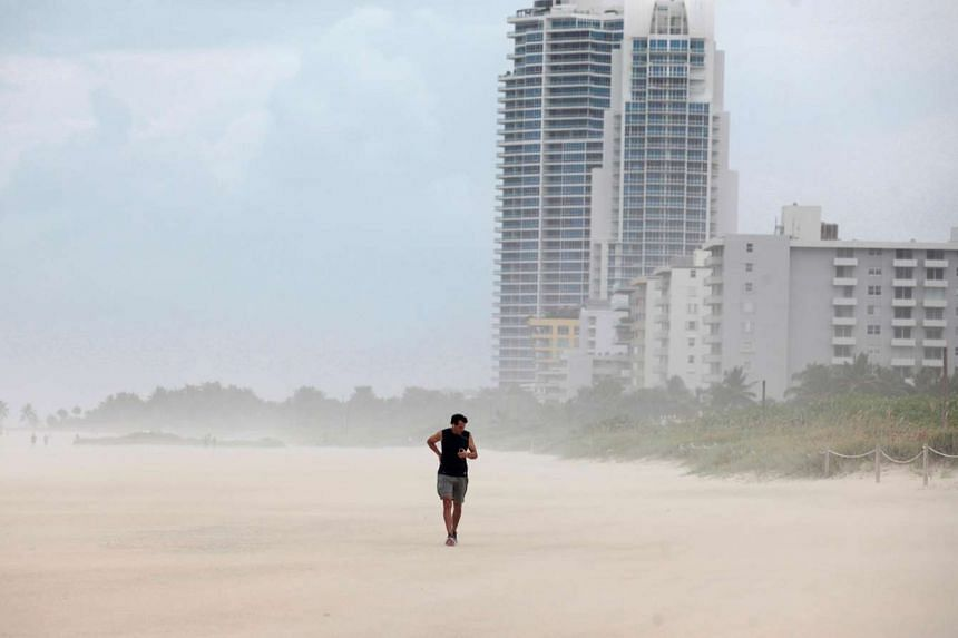 A person walks along the beach prior to the arrival of Hurricane Matthew in Miami Beach, Florida, Oct 6, 2016.
