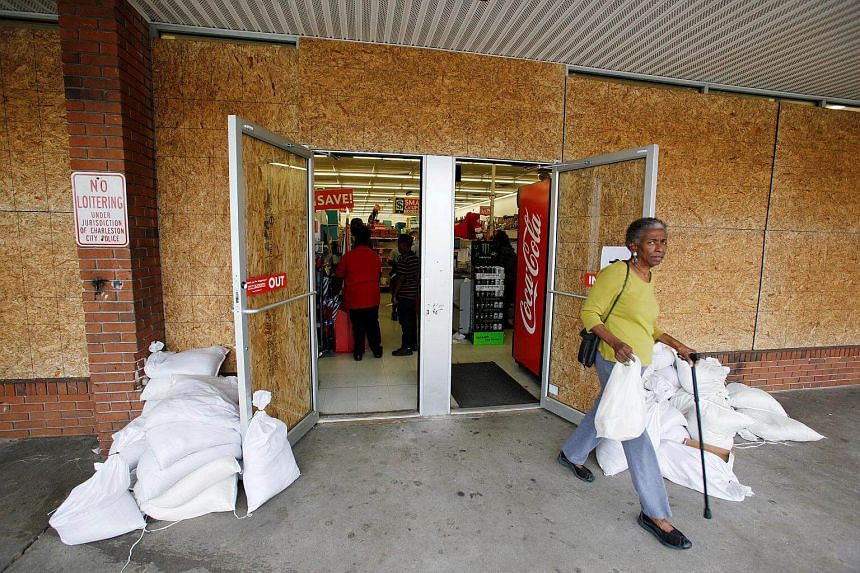 A Charleston resident walks past sandbags as she leaves a store that is boarded up in preparation for the arrival of Hurricane Matthew, in Charleston, South Carolina, on Oct 6, 2016.