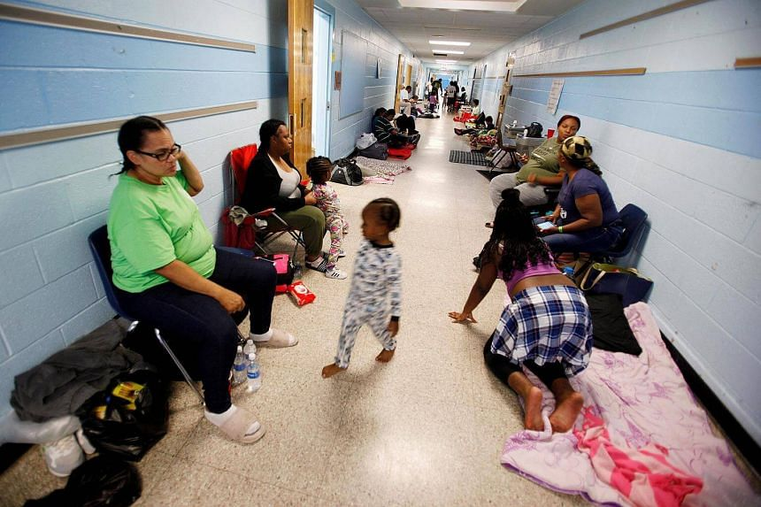 Residents of Charleston occupy a school hallway at a shelter ahead of the arrival of Hurricane Matthew, in North Charleston, South Carolina, on Oct 6, 2016.