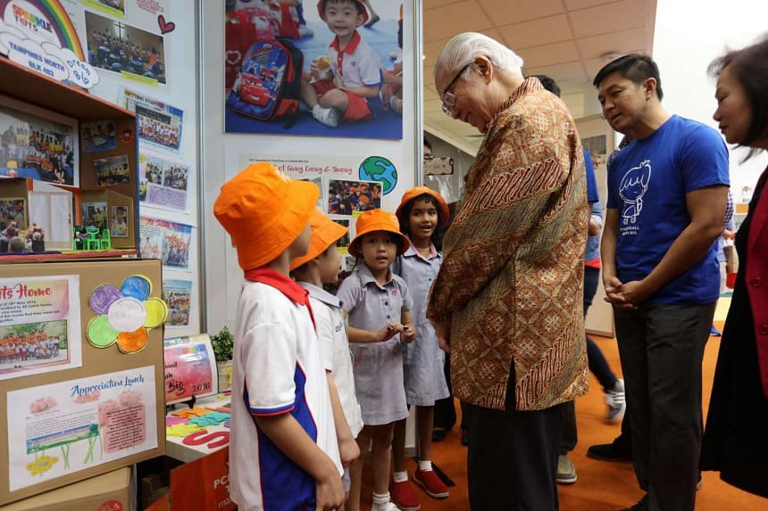 """President Tony Tan (centre) and Minister Tan Chuan Jin (in blue t-shirt) viewing a booth by pre-school students from Sparkle Tots during the President's to Early Childhood Development Agency's """"Start Small, Dream Big"""" finale at the Singapore Sports H"""