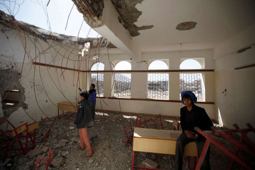 Boys in a damaged class of their school which was hit by Saudi-led air strikes last year, as schools open this week in Sanaa, the capital of war-torn Yemen on Oct 5, 2016.