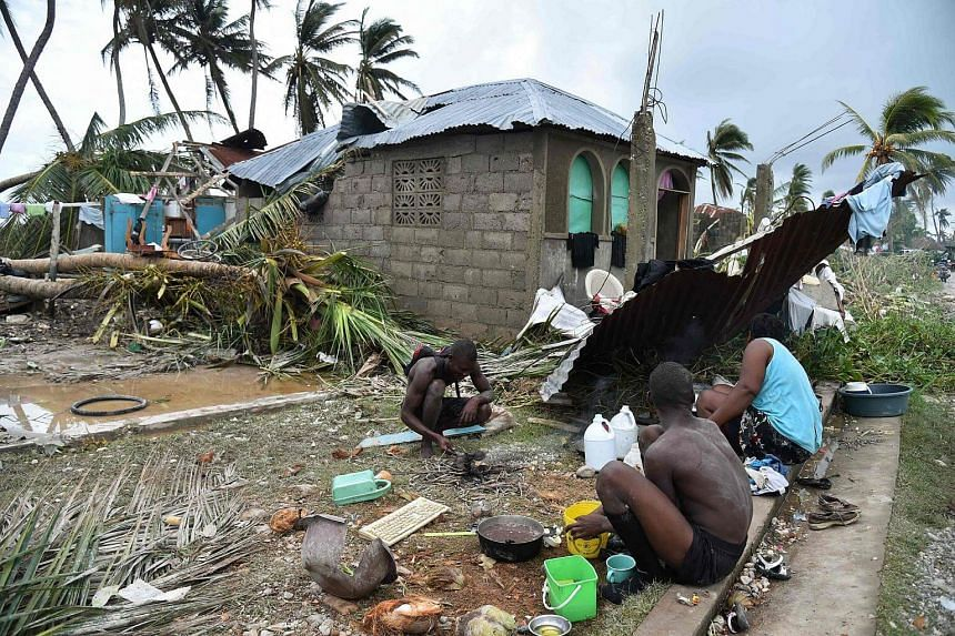 A family preparing food in front of a destroyed house after Hurricane Matthew, in Croix Marche-a-Terre, in south-west Haiti, on Oct 6, 2016.