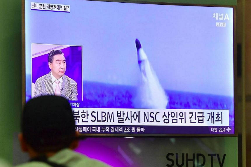 A man watching a television news showing file footage of a North Korean missile launch at Incheon airport, west of Seoul, on Aug 24, 2016.