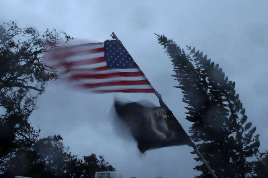 Flags blow in the winds of Hurricane Matthew, Oct 7, 2016 on Cocoa Beach, Florida.