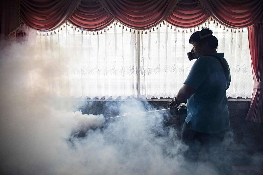 A city worker spraying chemicals with a fumigator to kill mosquitoes in an effort to control the spread of the Zika virus at a school in Bangkok.