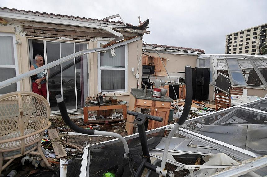 Homeowner Joe Lovece surveys the damage to the kitchen at the back of his oceanfront home after the eye of Hurricane Matthew passed Ormond Beach, Florida on Oct 7, 2016.