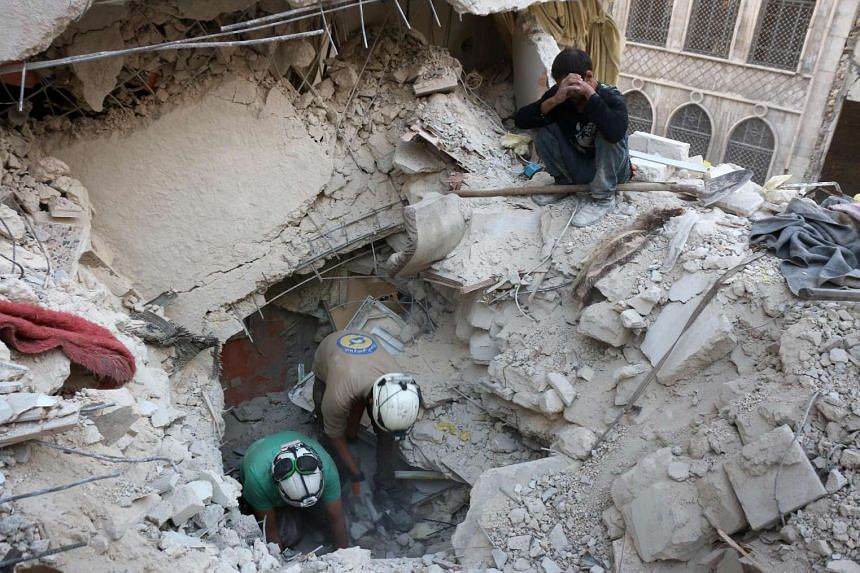 Syrian civil defence volunteers, known as the White Helmets, search for victims amid the rubble of destroyed buildings following a government forces air strike on the rebel-held neighbourhood of Bustan al-Basha in the northern city of Aleppo, on Oct