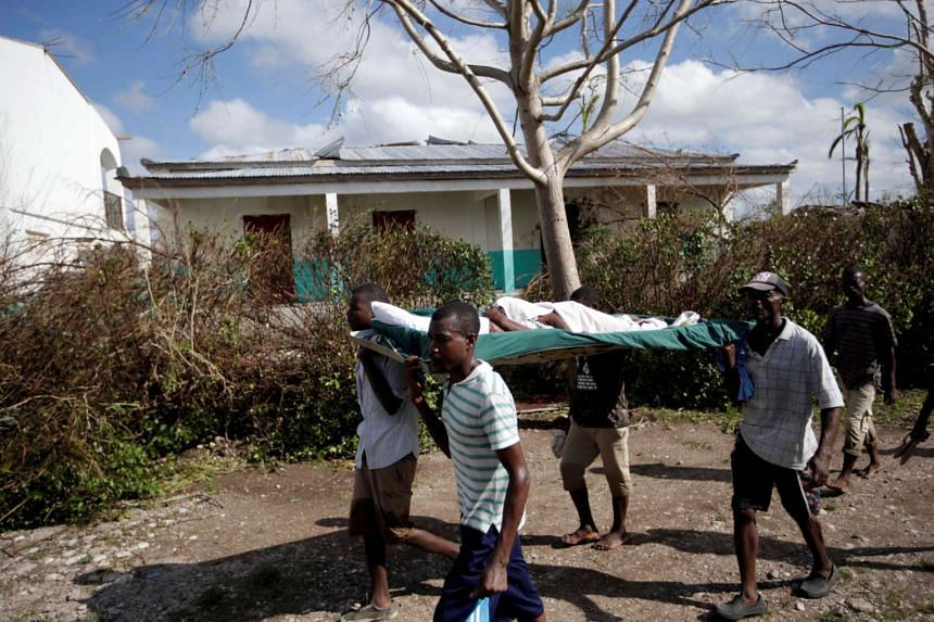 Men carry a woman wounded in Hurricane Matthew in Chantal, Haiti Oct 7, 2016.