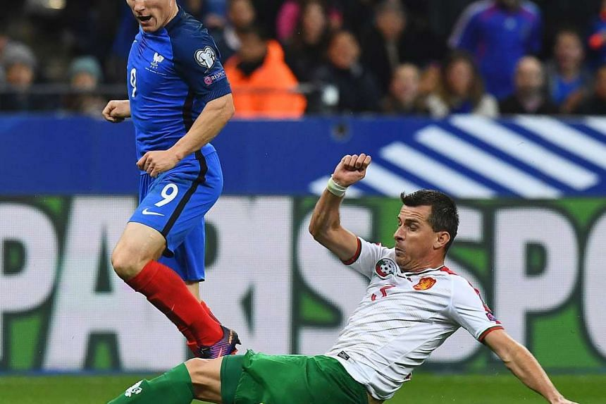 France's forward Kevin Gameiro (left) is tackled by Bulgaria's defender Aleksandar Aleksandrov during the Fifa World Cup 2018 qualifying football match France vs Bulgaria on Oct 7, 2016 at the Stade de France stadium in Saint-Denis, north of Paris.