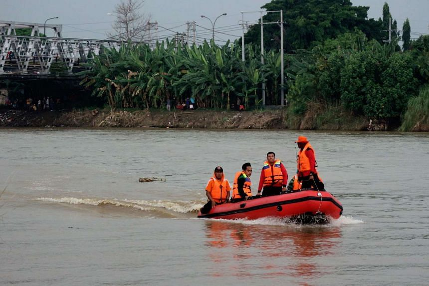 Rescuers search for missing teenagers at the Bengawan Solo river in Tuban, East Java province, on Oct 8, 2016 after a wooden boat carrying 25 boarding school students capsized.