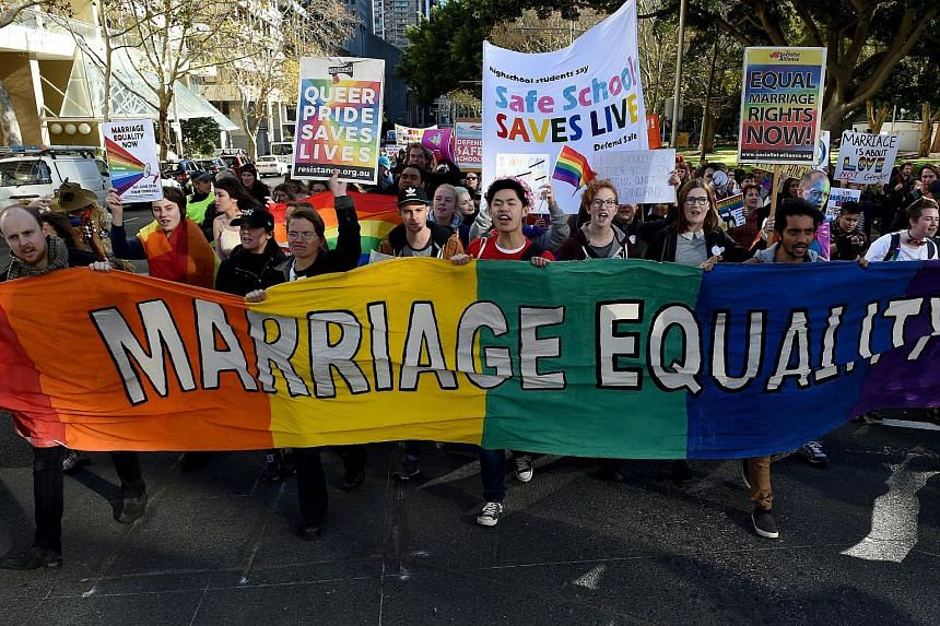 Pro-gay marriage supporters carrying a rainbow banner and flags during a rally in Sydney on June 25, 2016.