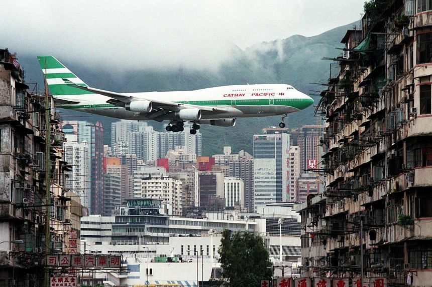This file photo taken on July 6, 1998, shows Cathay Pacific Boeing 747-400 jumbo jet flying over the Kai Tak Airport control tower.