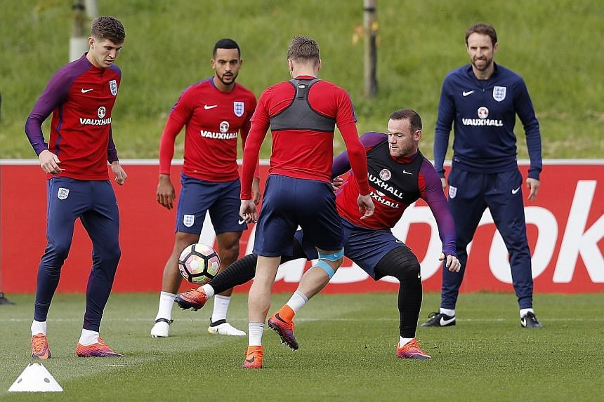 England players (from left) Theo Walcott, Jamie Vardy (back facing) and Wayne Rooney during a training session as caretaker coach Gareth Southgate looks on.