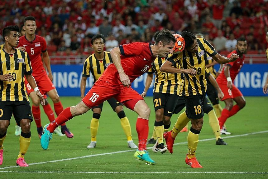 Singapore defender Daniel Bennett (No. 16) and Malaysia forward Hazwan Bakri (No. 18) challenge for the ball during the stalemate at the National Stadium.