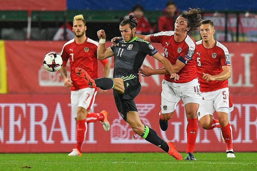 Wales forward Gareth Bale (centre) keeps possession as Austria's Julian Baumgartlinger lurks. Marko Arnautovic (No. 7) and Kevin Wimmer (No. 5) both made crucial touches during the World Cup qualifier. Arnautovic netted a brace while Wimmer scored an