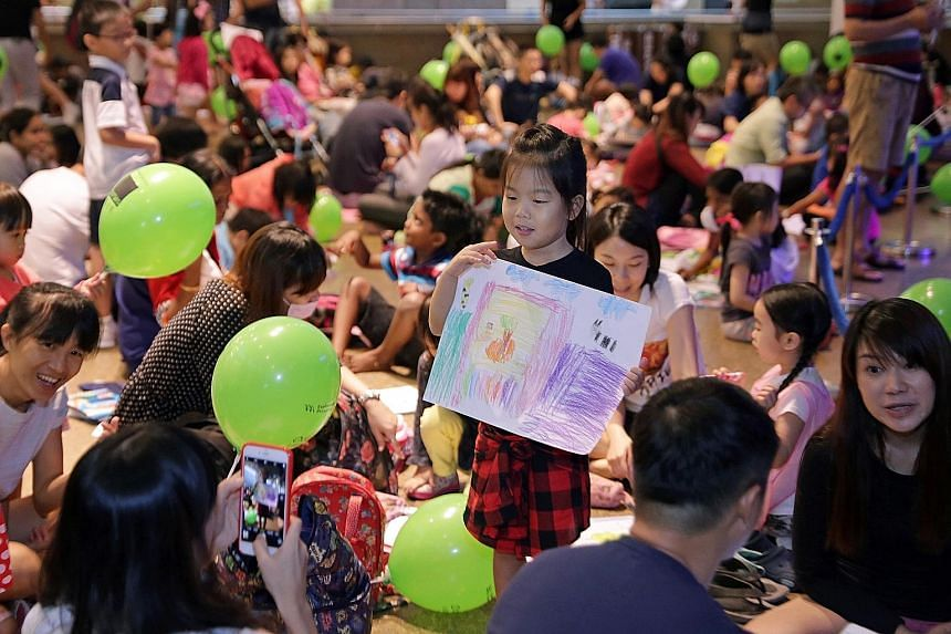 Five-year-old Lim Yu Han poses with her artwork for her mother, 38-year-old Maggie Chen. The girl was among more than 1,600 children who spent Children's Day yesterday letting their creativity run wild at the Esplanade. While those between five and 1