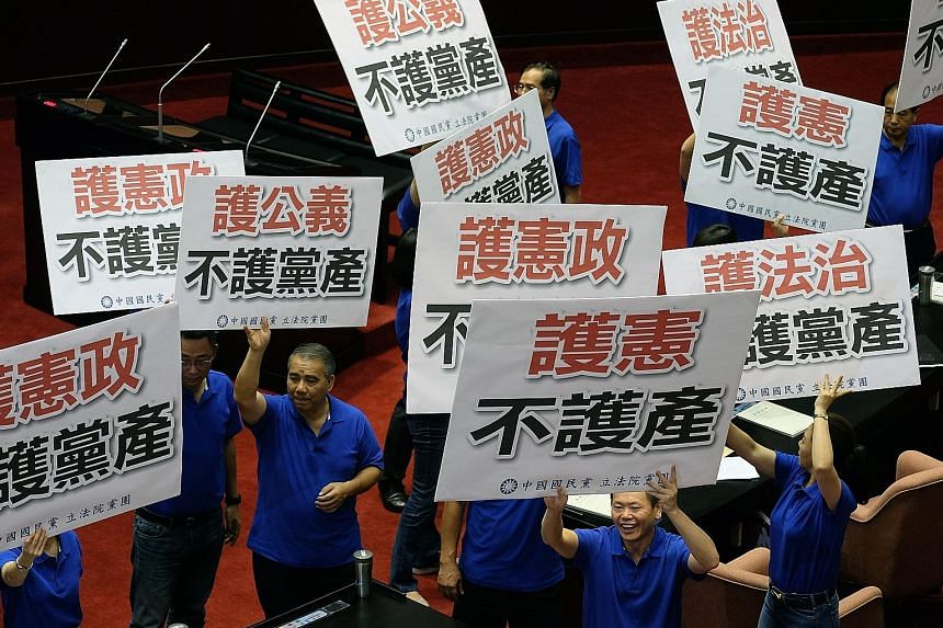 "KMT lawmakers with placards that read ""Protect the Constitution, not the party assets"", inside Taipei's Parliament in July. The current probe into whether the KMT had inappropriately amassed its assets is part of the transitional justice that Preside"