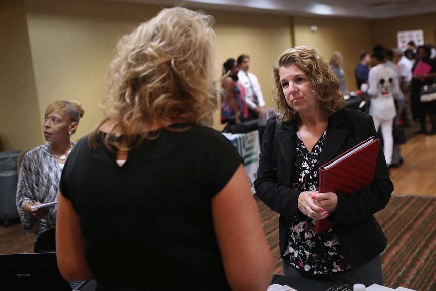 People carrying resumes speak with potential employers at a job fair on Sept 13, 2016, in Hartford, Connecticut.
