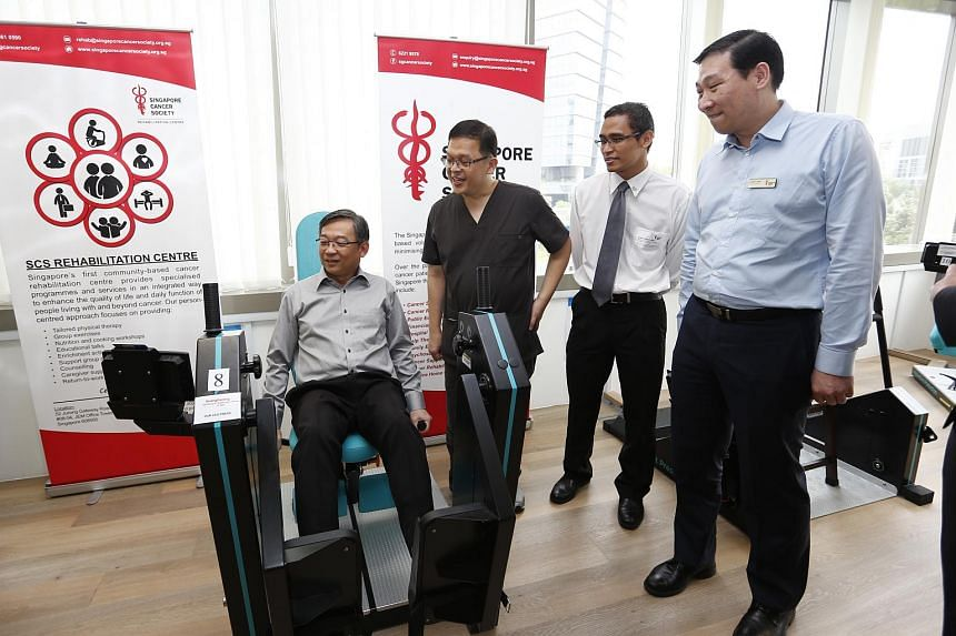 Health Minister Gan Kim Yong trying out the leg press at the SCS Cancer Rehab Centre's gym.