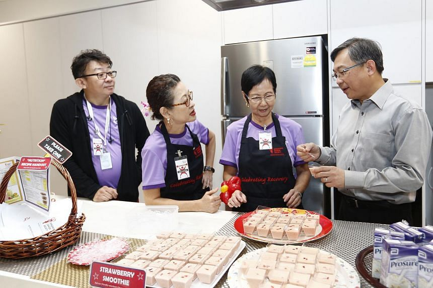 Health Minister Gan Kim Yong interacting with an SCS volunteer and cancer survivors in the kitchen at the SCS Cancer Rehab Centre.