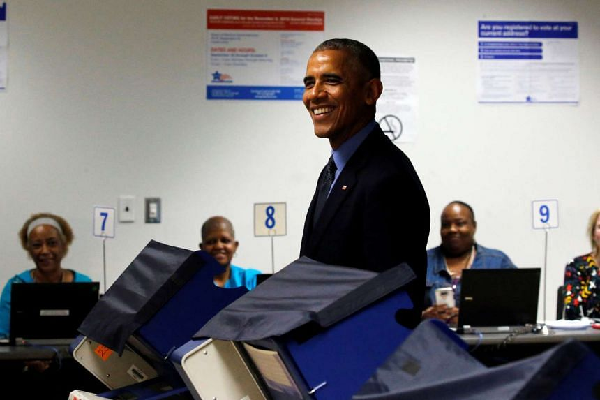 Obama looks up and smiles at reporters as he casts his vote for president.